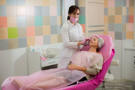 The cosmetologist looks into the camera and wipes the face of the patient Stock Photo