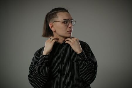 A young man with a fashionable unusual hairstyle adjusts