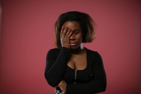 Facepalm. An African-American woman with a red manicure covers half of her face with her hand.