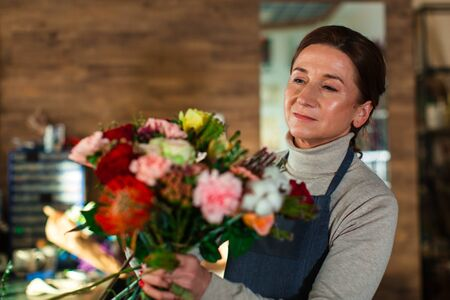 An elderly flower girl collects a bouquet of flowers. Stock Photo