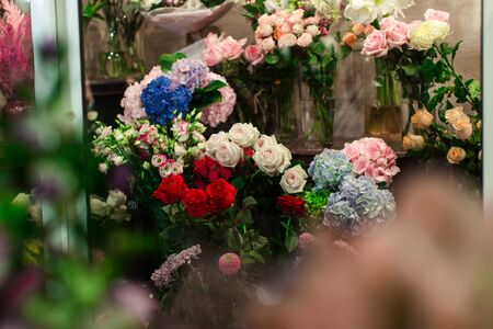 Flower shop counter with lots of bouquets of flowers. Red roses, white roses, blue flowers, blue flowers, yellow roses