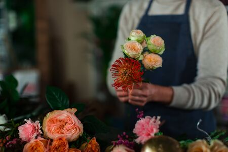 The hands of the florist assemble a bouquet of flowers of roses and Dahlia. Stock Photo