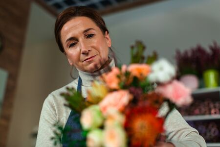 Portrait of a flower shop assistant with a bouquet in her hands.