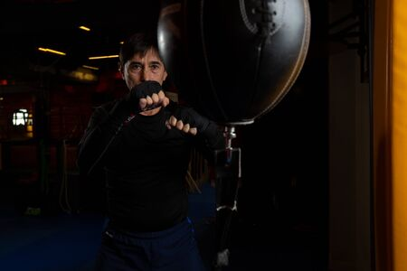 A mature male boxer in the gym. Training punches on a small punching bag. Professional trainer.