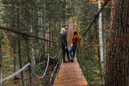 A young albino guy and a red-haired girl stand on in the woods on a suspension bridge and look at each other Stock fotó