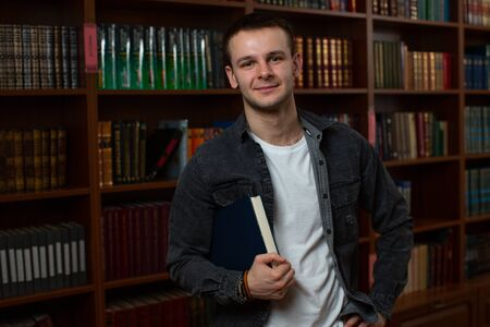 Portrait of a handsome young male student in a grey shirt and white T-shirt, looking at the camera and holding a book under his arm in a blue cover against the background of bookcases in the library