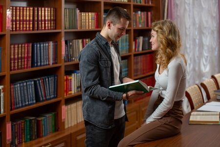 A couple of loving students talk in the library discussing what they read in the book. The girl blonde looks in love at the young man in a gray shirt, which explains to her the material from the book.