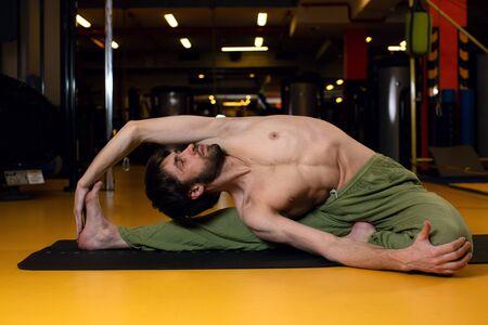 A young man performs a complex position parivritta Janu Shirshasan. professional yoga. An inverted tilt to the knee. Man practicing the parivritta pose of Janu Shirshasana 写真素材