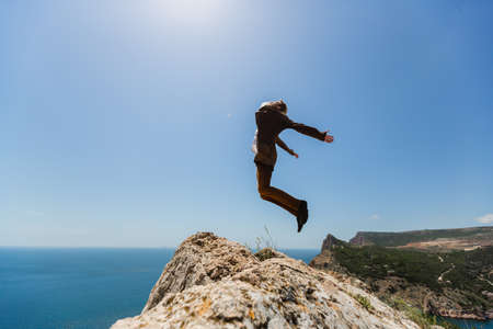 The silhouette of a young man in a brown suit, standing on the edge of a cliff and jumping in the pose of a flying bird with his hands divorced against the bright blue sky and scorching sun
