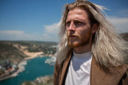 A young, handsome man with long blond hair developing in the wind, in a brown jacket and white T-shirt, stares intently into the distance against the backdrop of the valley into which the sea flows