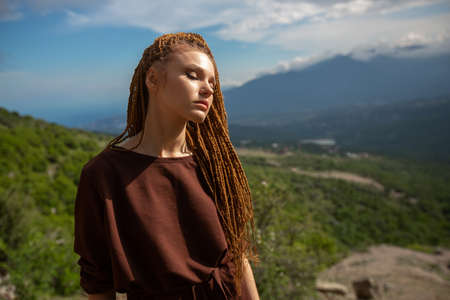 Portrait of a girl with an informal appearance, disdain expression of the face, hair in fine pigtails, in a brown T-shirt against the backdrop of mountainous terrain and cloudy sky