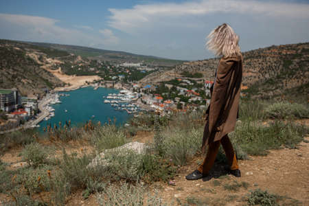 A young man with blond hair up to his shoulders in a brown robe, stands on top of a mountain and contemplates the incredible view of the Crimean seaport and coastal area Banco de Imagens