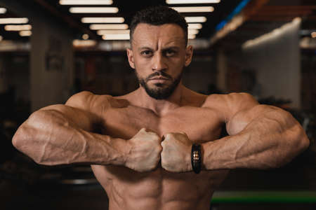 A handsome, handsome bodybuilder with swung back muscles and hands poses looking at the camera and joining his fists at chest level against the backdrop of the gym