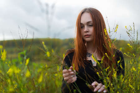 A brooding red-haired girl with a sad face in a black jacket stands among the high wildflowers in the field. Stockfoto