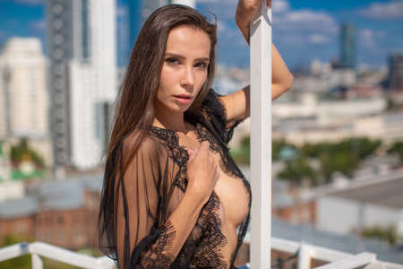 Beautiful brunette girl with large breasts in a black lace wrapper over her on a naked body, looks at the camera standing at the white fence on the roof of the house city panorama in the background