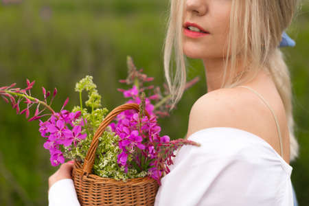 Young blonde woman walks in the countryside holding a basket with wild pink flowers