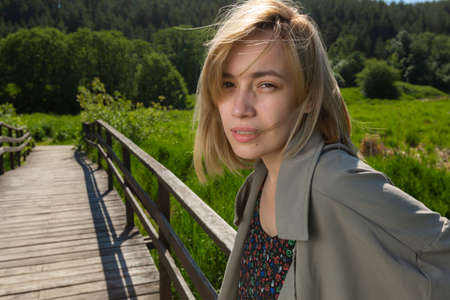 A young blonde girl in a gray cloak stands on a wooden bridge mysteriously looking into the camera against the background of green forest in sunny weather. Bright sunny day. Summer mood.