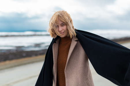 Romantic blonde in a beige coat stands on the highway in windy weather mysteriously looks into the camera, hair flying from the wind. Winter landscape. A lonely walk. High quality photo Stock fotó