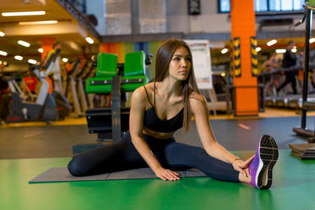 Sexy young girl in sportswear sits on the gym mat doing stretching in the gym and looking ahead. Photos for fitness instructors and gyms. High quality photo