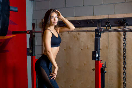 A young woman with long hair in sportswear stands leaning on the simulator in the gym. Photos for gyms and fitness instructors. High quality photo