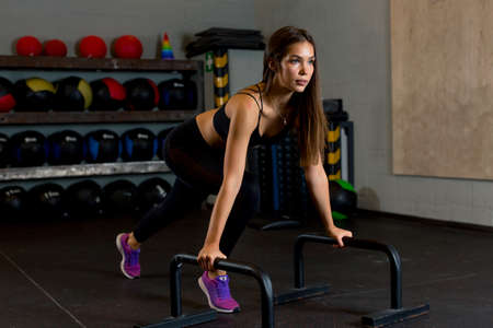 Slender girl athlete with long brown hair performs physical exercises in the gym against the background of sports colored balls. Photos for advertising sports equipment or clothing. High quality photo