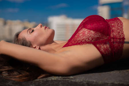 A young girl with a large bust lies on the roof of a building in a red bra against the backdrop of a big city. High quality photo