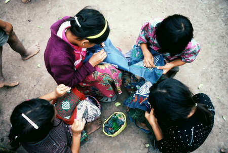 refugee: Hmong girls from Laos sewing traditional paj ntaub in Chiang Kham Refugee Camp, Thailand