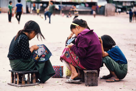 Hmong girls from Laos sewing traditional paj ntaub in Chiang Kham Refugee Camp, Thailand