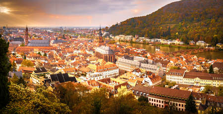 A landscape view of the city of Heidelberg, Germany taken during a Fall evening showing the citys bridge over the Neckar river, cathedrals and Fall foliage in the background Stock Photo