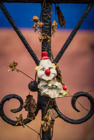 A neglected and sad looking clown toy is mounted on an iron fence with decaying plants around it