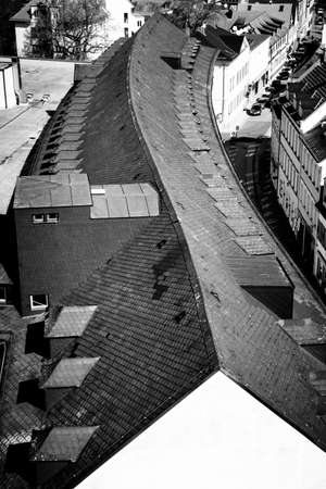 s curve: Black and white image of the roof of a long building with an S-curved ridge line