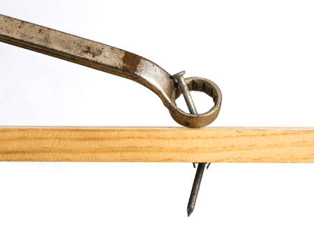 An wrench is shown attempting to be used to pry a nail from a piece of wood