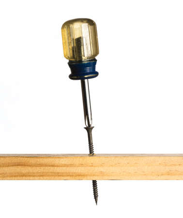 A screwdriver rests atop a large sharp screw in a piece of wood