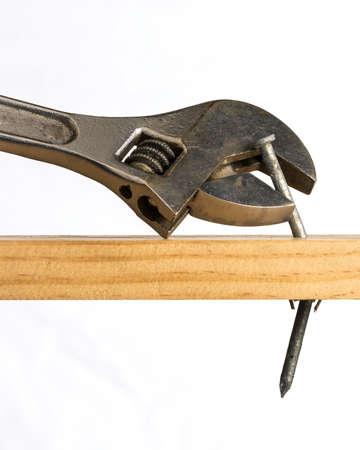 調整レンチは、木片から釘を詮索するために使用されることを試みて示されています