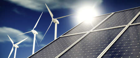 Solar panels or collectors and wind turbines infront of blue sky with clouds in sunlight Stockfoto