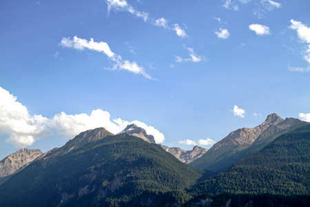 View of high mountains in the Swiss Alps in Grisons on a slightly cloudy day in summer