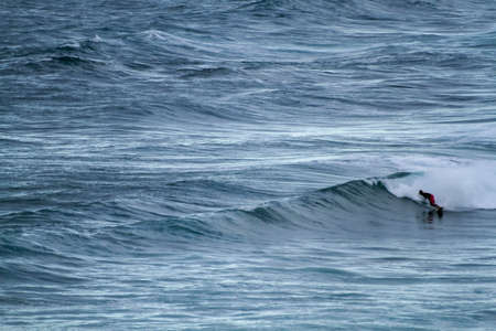 A surfer sportingly rides down a wave on a beach in Portugal on the Atlantic Ocean Standard-Bild