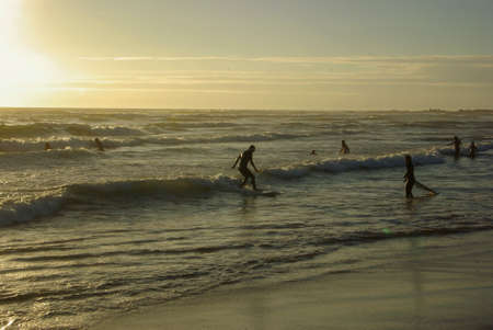 Surfers having surf lessons riding down small waves in sunset on beach in spain