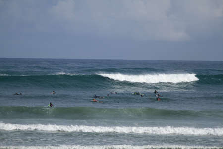 Many surfers sit and lie on their surfboards between breaking approaching waves on a beach in Portugal on the Atlantic Ocean Standard-Bild - 163764812