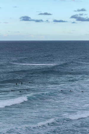 Many surfers sit and lie on their surfboards between breaking approaching waves on a beach in Portugal on the Atlantic Ocean