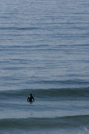 A surfer lying on his surfboard paddles over an approaching wave on a beach in Portugal on the Atlantic Ocean Standard-Bild