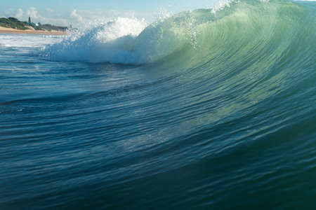 Breaking waves and spray, white water and light reflecting on the surface of the moving water