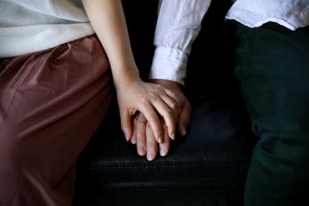 Man and woman holding hands on the couch Stock Photo
