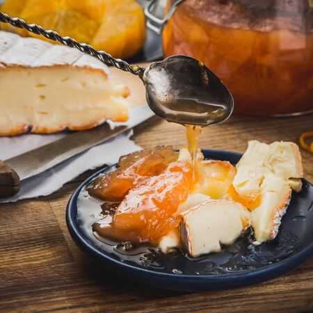 confiture: Still life with  the pieces of cheese and confiture on the blue plate and the antiquarian spoon Stock Photo