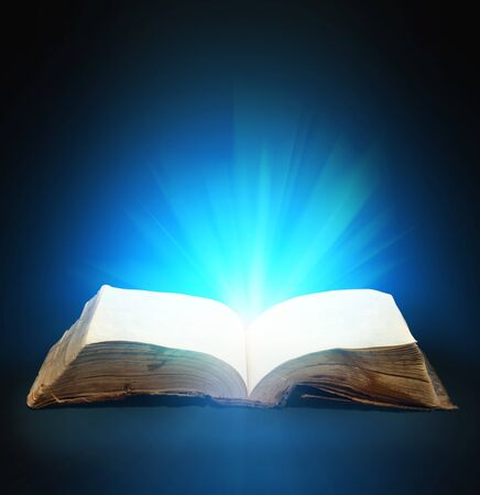 Opened magic book with magic light for you design photo