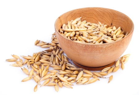 handful of crops of oats in the wooden saucer on a white background photo
