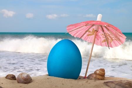 Huevo de Pascua en la playa bajo un paraguas Foto de archivo