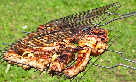 charbroiled: fried chicken wings on fire and pork ribs Stock Photo