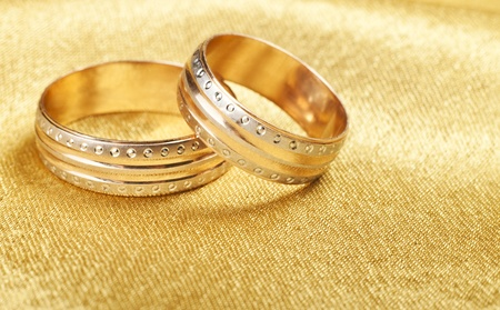 Gold wedding rings lying on silk photo