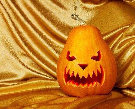 Sang orange pumpkin on the golden silk Stock Photo - 10640496